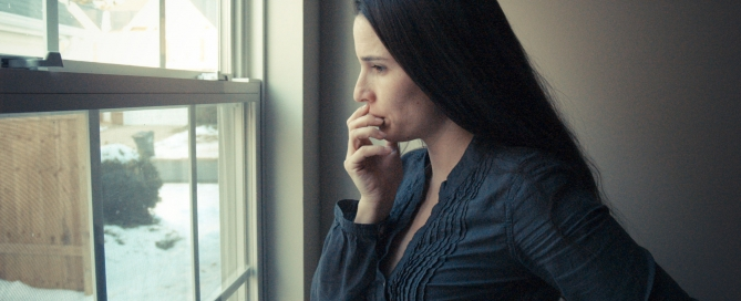 depressed female looking out window