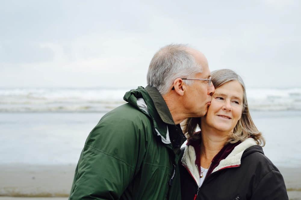 older couple kissing at the beach